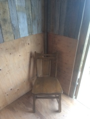 Old chair in rustic maqii steam bath house with drift wood and old pallet boards.