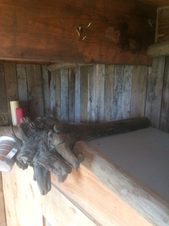 Rustic maqii steam bath house with drift wood and old pallet boards.